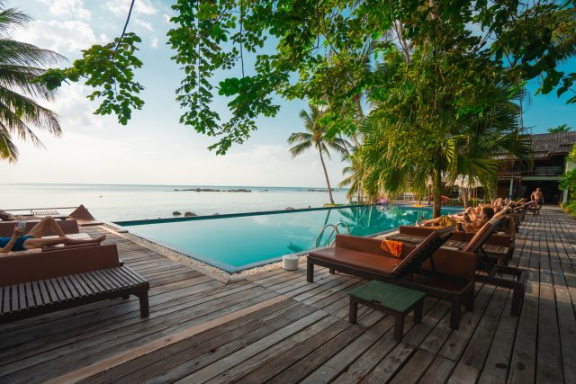 brown wooden table and chairs on brown wooden deck near body of water during daytime